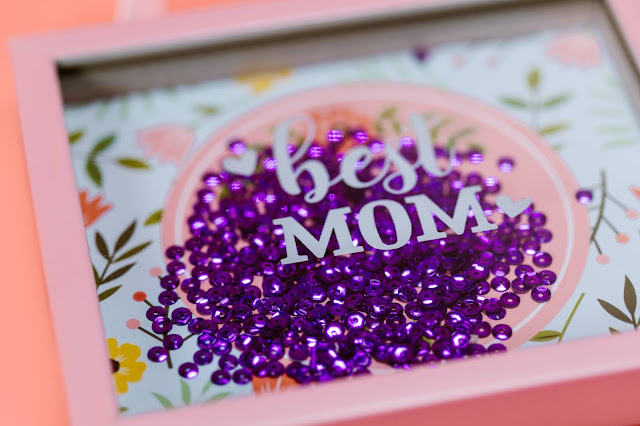 """Purple sequins inside a pink gift box with """"BEST MOM"""" printed on top."""