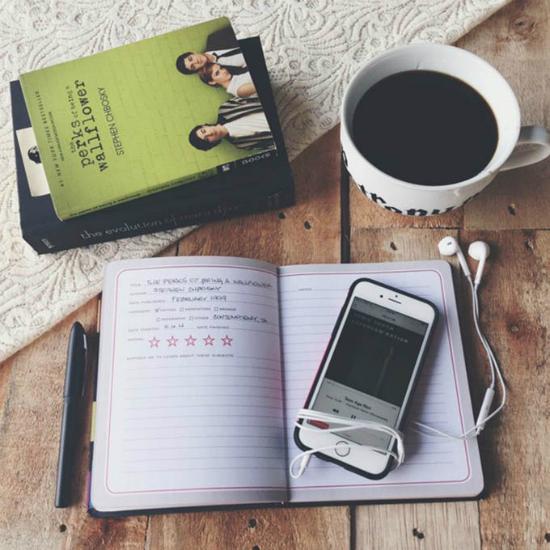 livros, uma xícara de café, um caderno e um celular