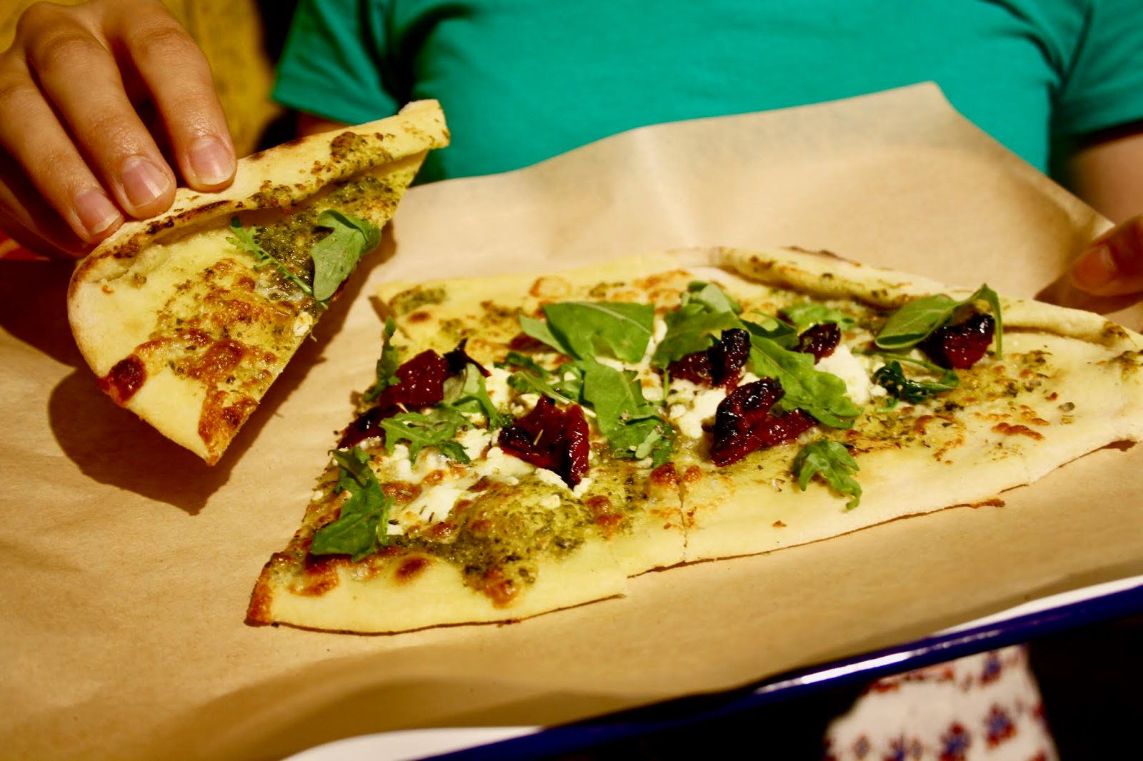 Abbey holds a slice of pesto and feta pizza up towards the camera