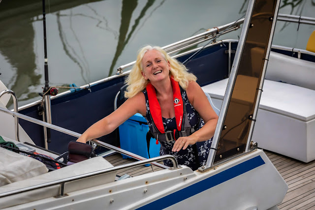 Photo of me reaching for my camera as we left the marina on Ravensdale. Photo by Ronnie Bell
