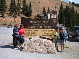 Four ladies with their hiking gear on taking a photo at the Continental Divide sign on Monarch Pass.