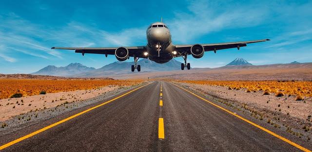 Foto de avión comercial frontal despegando con carretera en primer plano, fondo de montañas y cielo azul