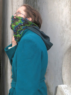 A woman wearing a crochet lace cowl done in a variegated yarn. The cowl is pulled up over her mouth and nose