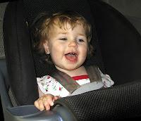 smiling toddler in car seat