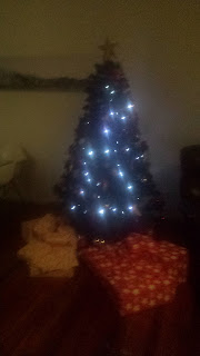 Photo of Christmas tree with lights and presents under it