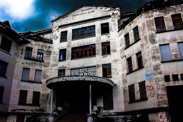 photo de l'ancienne entrée du sanatorium vu de l'extérieur avec un ciel sombre à l'orage