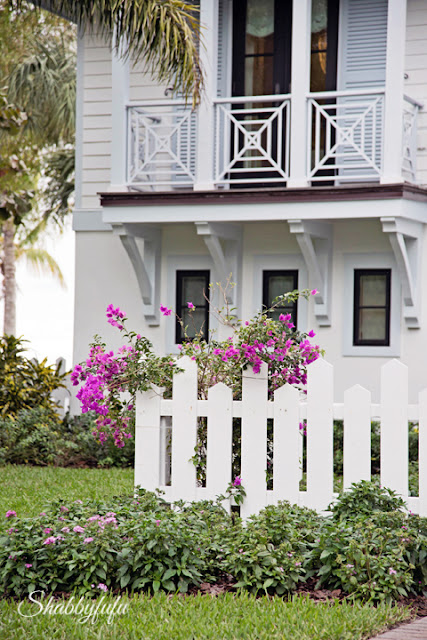 Details of the front of the HGTV Dream Home 2016 - the white picket fence, second-story balcony railing, and landscaping.