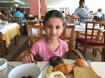 Child with treats from a breakfast buffet in a hotel