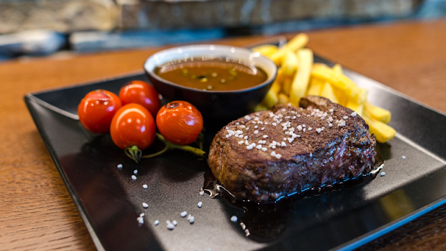 a steak topped with rock salt, with a side of grilled cherry tomatoes