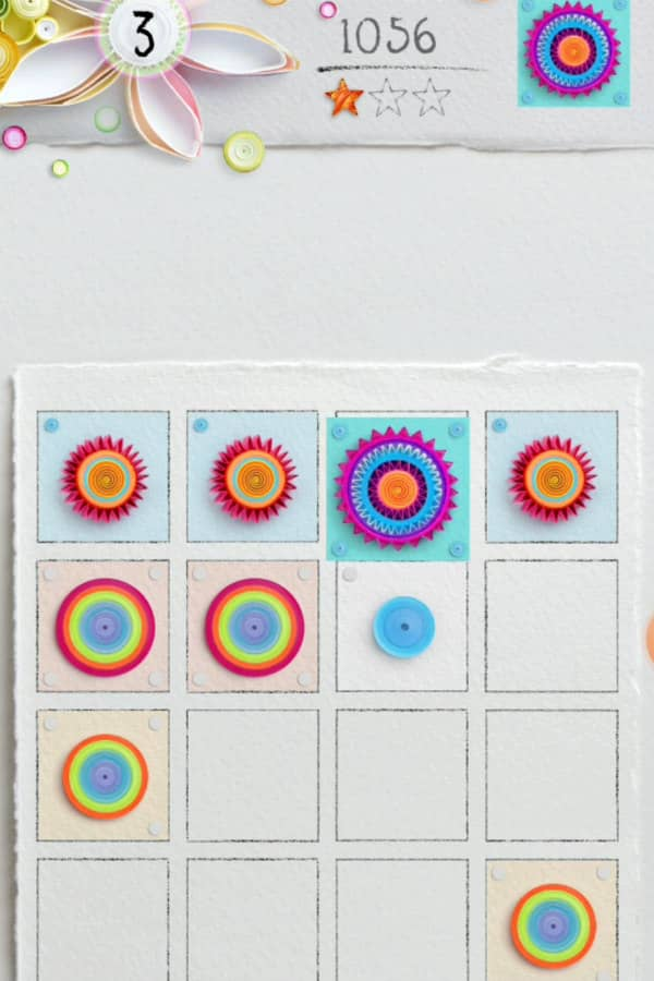 image of mobile game board shows colorful circular discs and floral on edge paper art