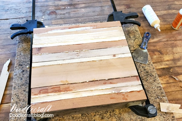 After placing the last board on the stack, hold them in place firmly with the c clamps. Then let the glue dry and cure overnight.