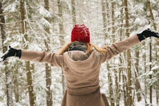 A lady appreciating the beauty of nature in a snow covered woods