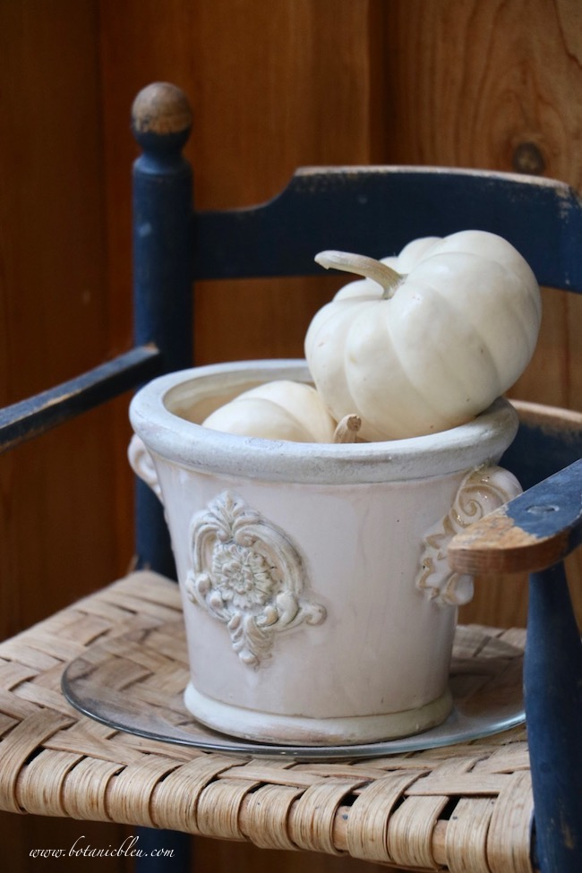 Easy inexpensive fall decor on a vintage blue high chair with pumpkins in a white French style urn
