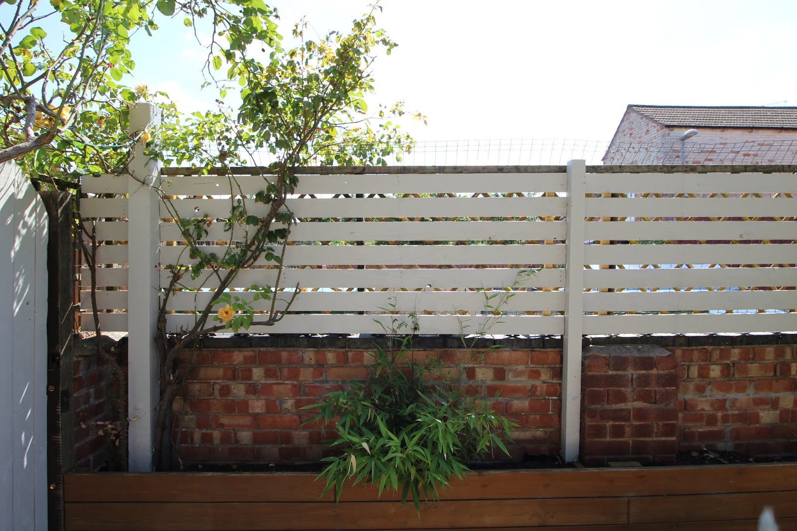Slat fence painted off white