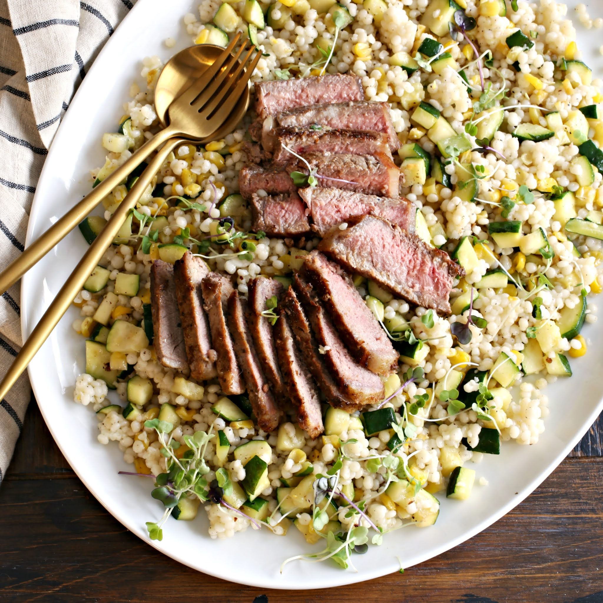 Recipe for sliced strip steaks on a bed of couscous, corn and zucchini salad.