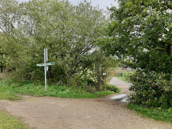 Turn right at the three-way sign, cross the bridge, and turn left on the lane Image by Hertfordshire Walker released via Creative Commons BY-NC-SA 4.0