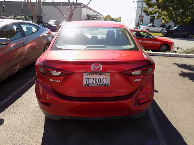 Mazda 3 bumper damage with 3-stage Soul Red paint before repairs at Almost Everything Auto Body.