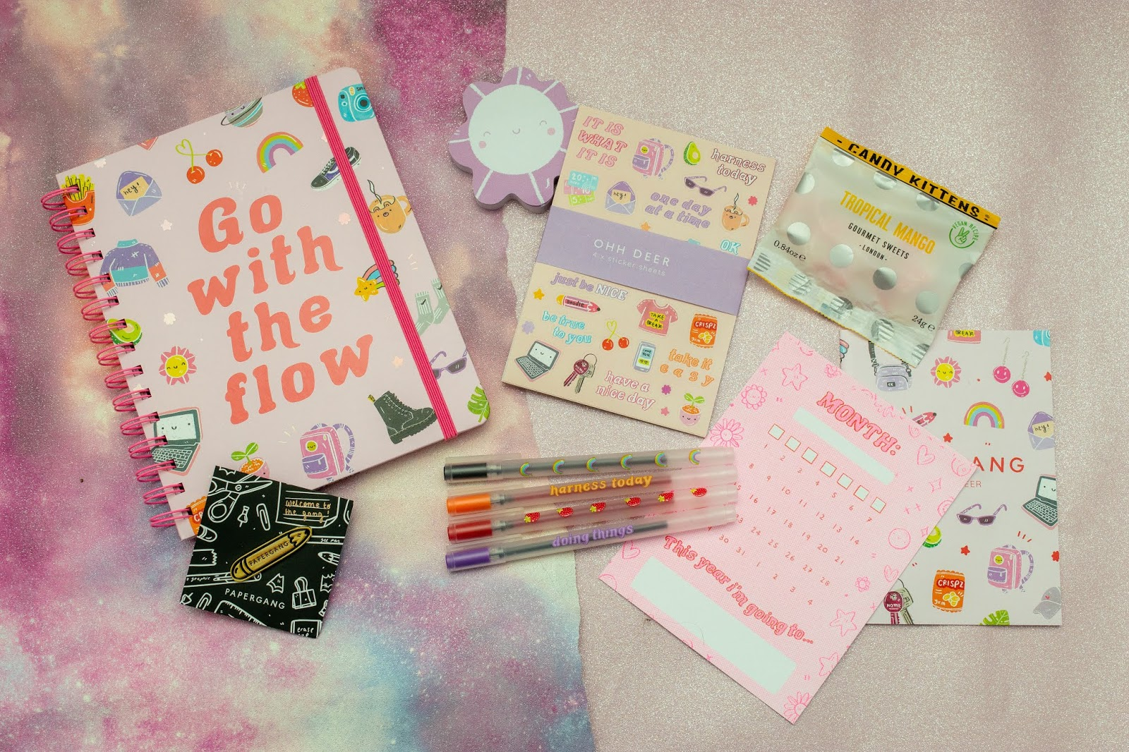 A flat lay of things including a spiral bound notebook, a pin, flower shaped paper notes, stickers, four pens, a postcard and a packet of sweets.