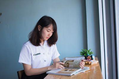 Tips para leer mejor. Mujer sentada a la mesa junto a la ventana, leyendo un libro, con varias revistas y una planta