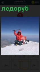 мужчина в красной куртке ледорубом рубит лед