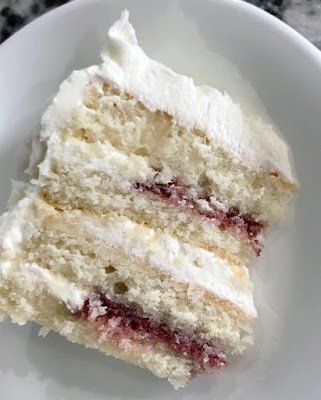 slice of cake with 4 layers of white cake, white frosting and raspberry filling