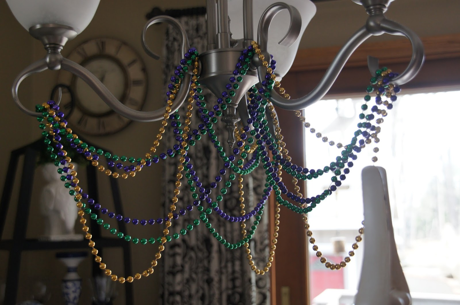 Home and gardening with liz nola inspired mardi gras tablescape i had fun draping the beads on the chandelier anyone who has visited ron at the uptown acorn will see many mardi gras images since he lives in the heart of arubaitofo Choice Image