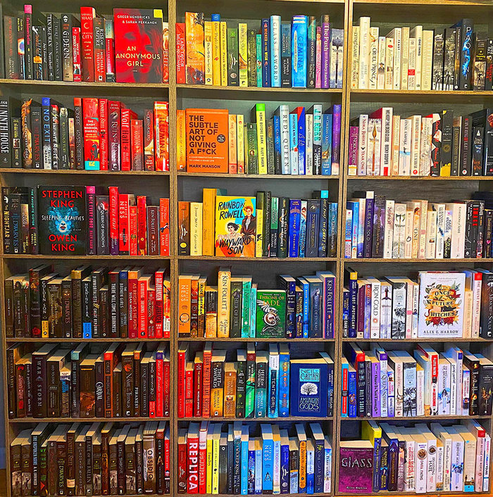Someone arranges books according to the color of the cover. And even if it took four hours.