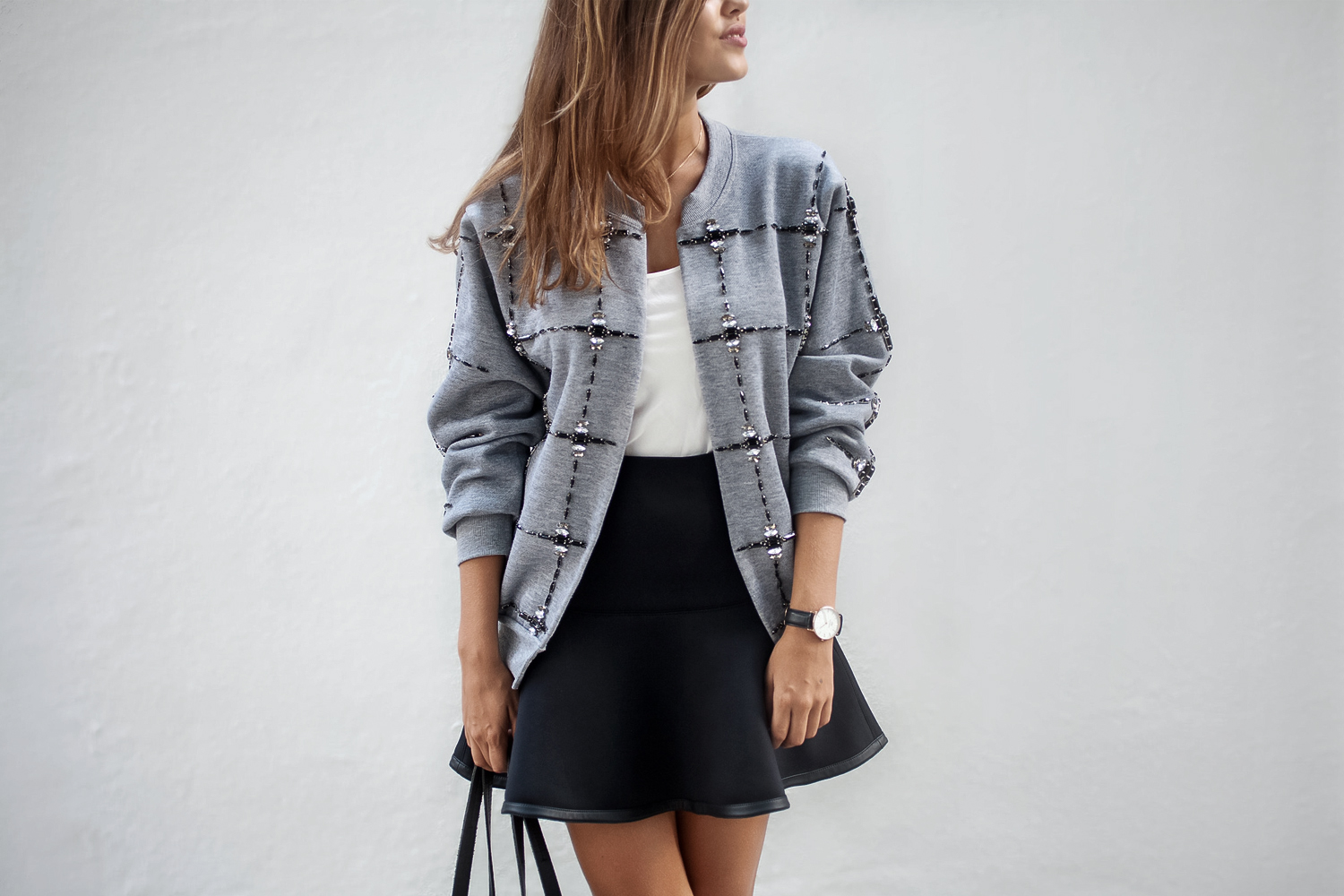 an unudentified women in a handmade bomber jacket and skirt on a plain background