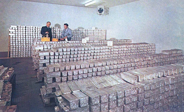 silver ingots stacked in storage in a color photograph