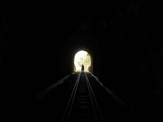 Imagem ilustrativa de um conto de terror, foto contendo uma luz no fim de um túnel escuro, cena de conto de terror