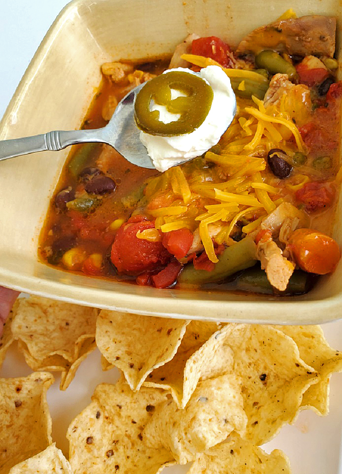 this is a bowl of southwest soup with chips, sour cream and jalapenos