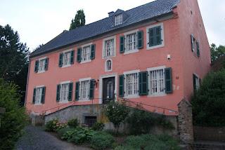 Ein Rösafarbenes Haus mit elf Fenstern an der Vorderseite und grünen Fensterläsen