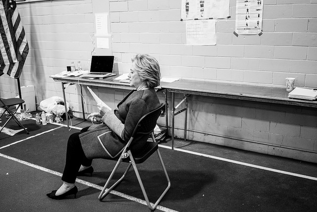 black and white image of Hillary Clinton backstage before a campaign event, sitting alone in a folding chair, studying something on a sheet of paper