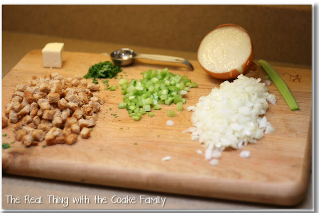 diced toasted bread cubes, butter, parsley, chopped celery and onion on cutting board