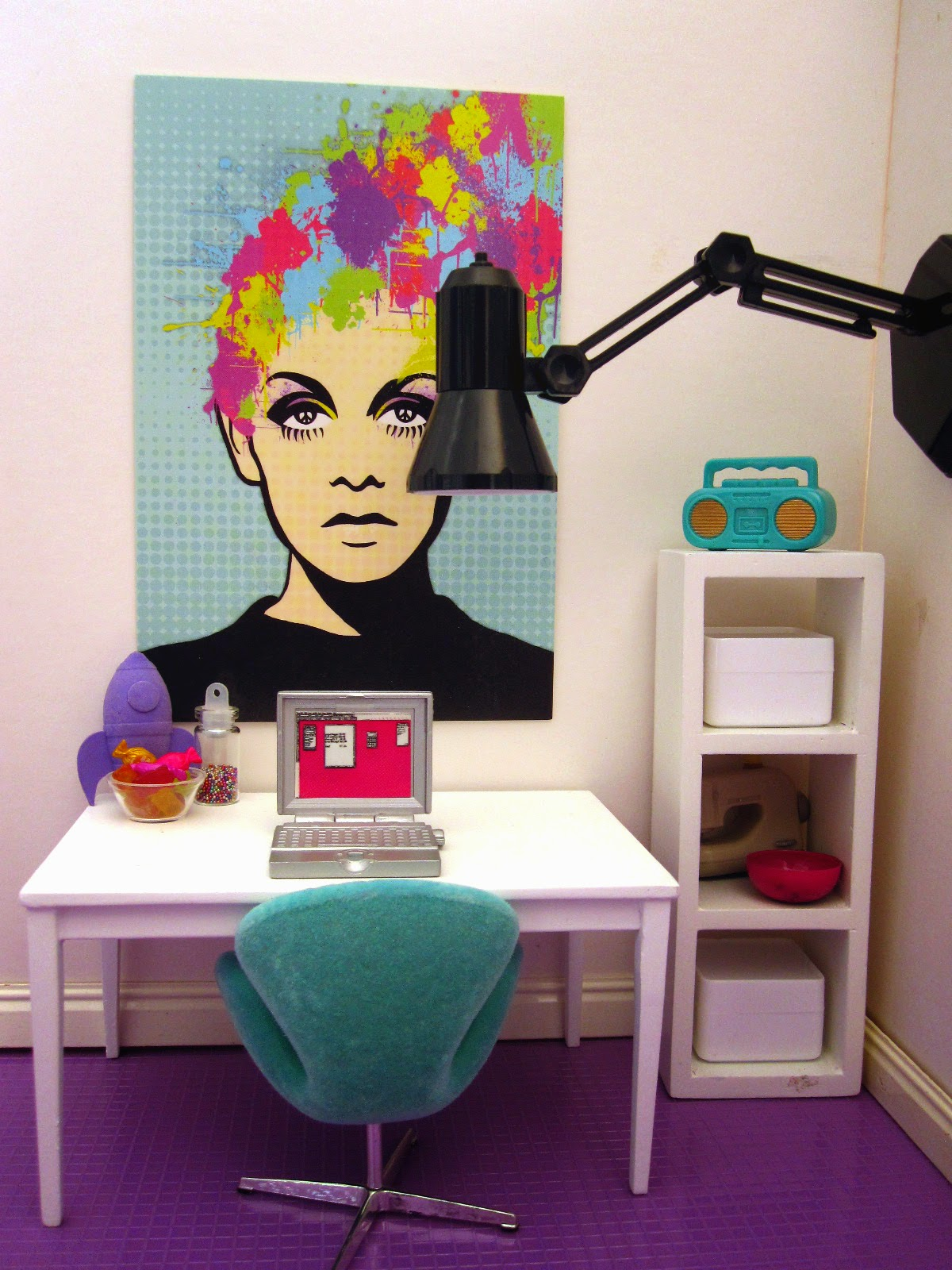 Modern dolls house miniature scene of a study with white walls and purple tiled flooring. A teal swan chairs sits in front of a white table with a laptop on it. A white shelving unitl is to the right and a large place lamp is attached to the right-hand wall.
