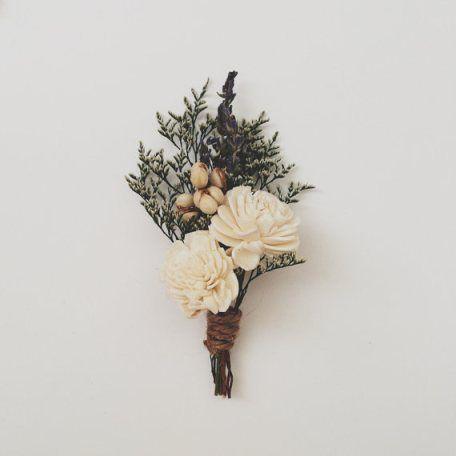 Un broche de plantas perennes con un estilo muy navideño en tonos blancos
