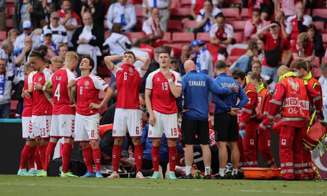Denmark players protecting Christian Eriksen from the camera