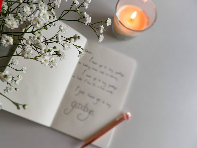 A book with blurred writing sits tilted to the left and open on a table. To the top right is a glass candle lit with a deep orange flame. The camera is focused on a small bunch of baby's breath that is closer to the camera