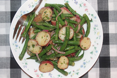 Bowl of green bean and red potato salad with a fork.