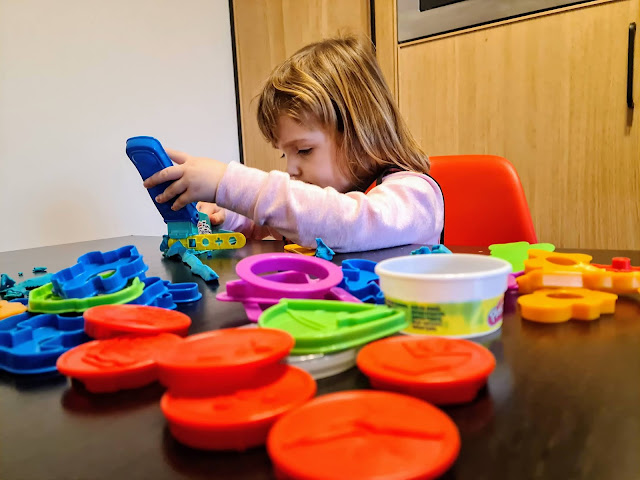 Image of a young girl sat at a black table playing with play doh. The girl has a look of concentration as she places Play Doh into a shape maker. Across the table lie many different Play Doh moulds and cutters.