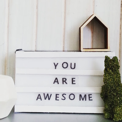 Modern dolls' house miniature scene with a light box (with the words 'You are awesome' on it), grass bunny, house-shaped wall box and a geometric marble vase.