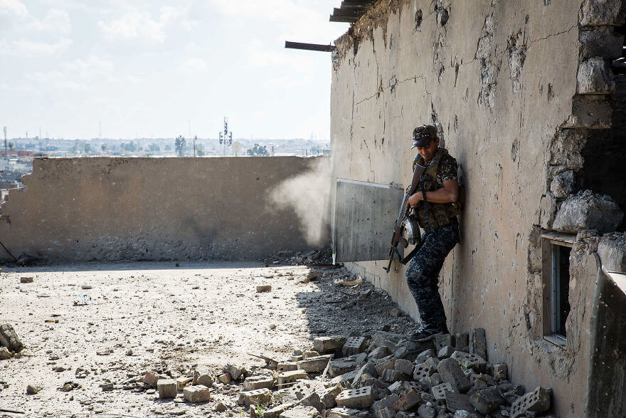 Powerful Heart-Breaking Pictures Of The Battle Of Mosul - A Federal Policeman takes fire from the other side of a theater. Several bullets impacted the other side of the wall near where he had been looking through a window