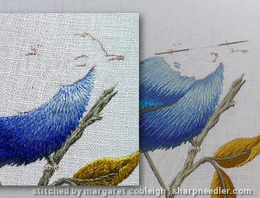 Embroidery under the head of a blue thread painted bird has been corrected to fix the direction of the stitching.