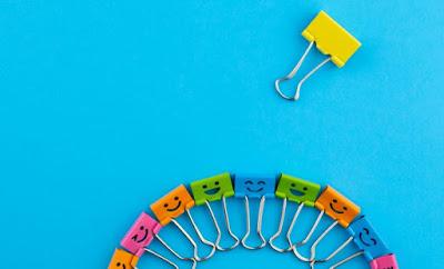 Descrição da imagem #PraCegoVer: Um semicírculo com vários prendedores de papel coloridos com carinhas felizes aparece no rodapé da imagem, quanto mais acima aparece um prendedor amarelo isolado sem expressão facial. Fim da descrição.
