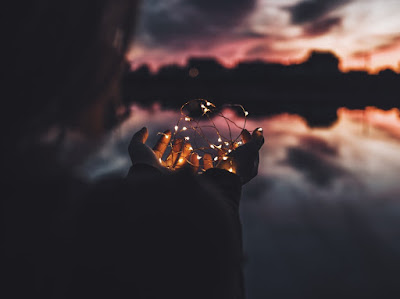 Sunset with a woman holding up fairy lights in the foreground