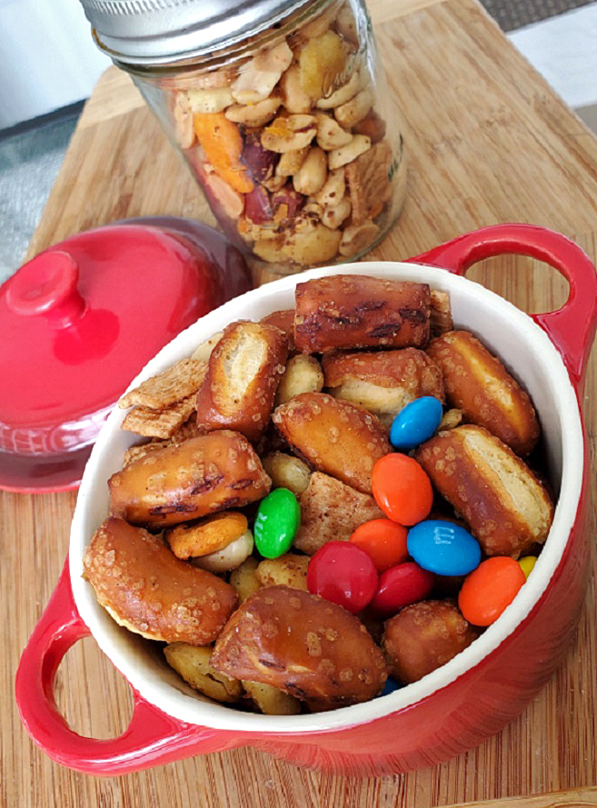 this is a red casserole dish with snack mix and a mason jar filled with cereal nuts and crackers mixed together