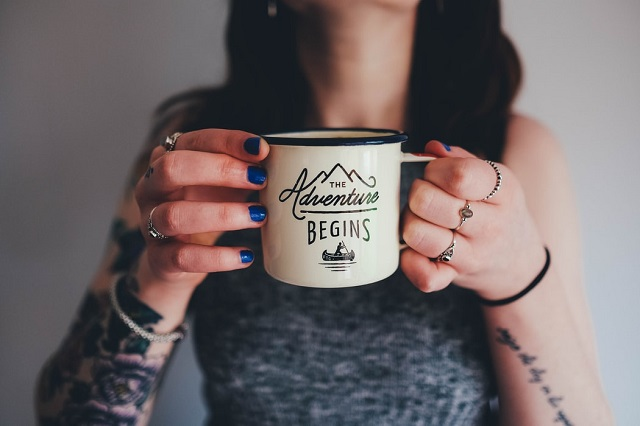 woman with tattooed arms holding adventure begins mug