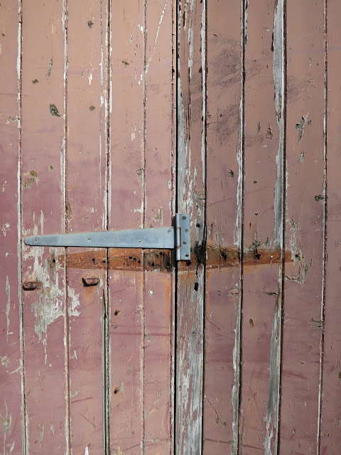 Unsecured metal clasp on wooden door with peeling brown paint.