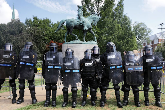 Virginia State Police in riot gear stand in front of the statue of General Robert E Lee