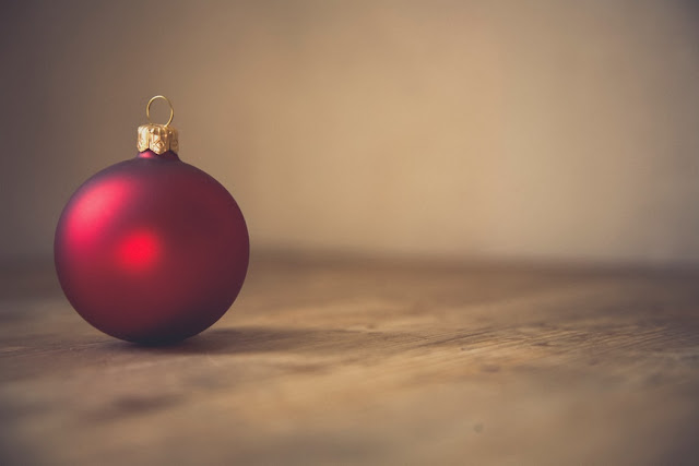 Single red bauble on a wooden table
